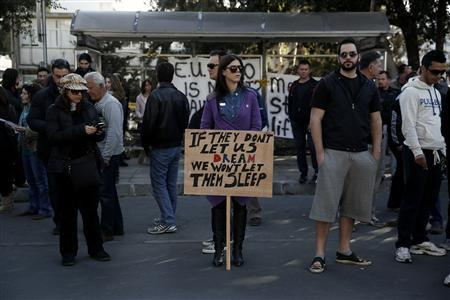 Protesters take part in an anti-bailout rally outside the parliament in Nicosia